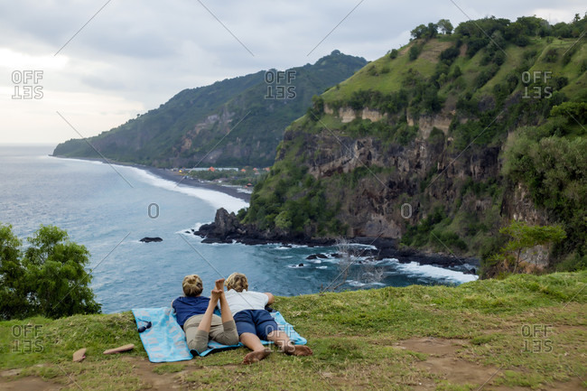 Adult couple lying together on blanket and admiring ocean coastline, Bali, Indonesia