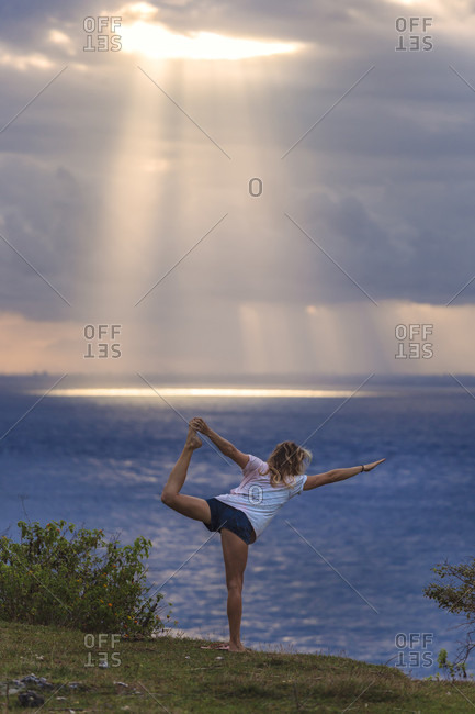 Back view of woman stretching by sea at sunset, Nusa Penida island, Bali, Indonesia