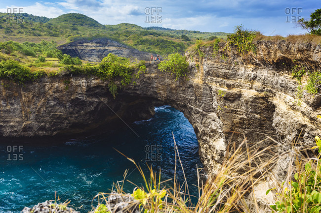 Family with three children on arch over ocean coastline, Nusa Penida island, Bali, Indonesia
