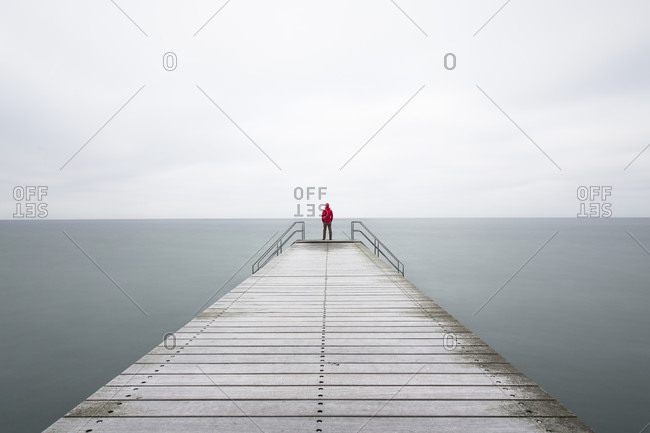 Person standing at end of pier in sea, Malmo, Skane County, Sweden