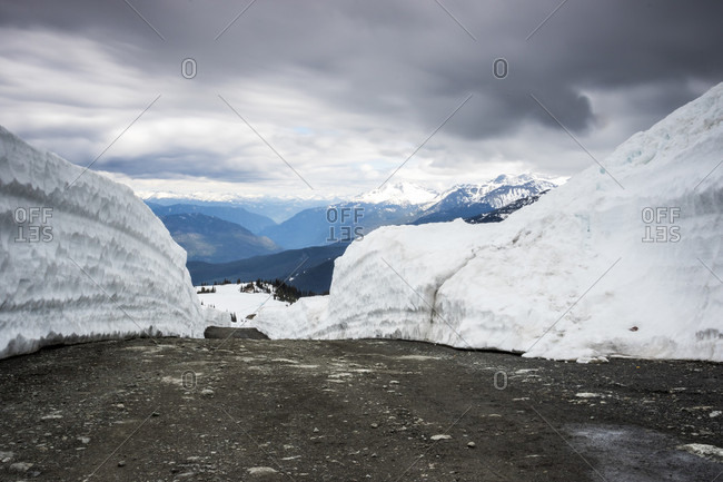Giant snow walls on sides of road plowed after winter, Whistler Mountain, Whistler, British Columbia, Canada
