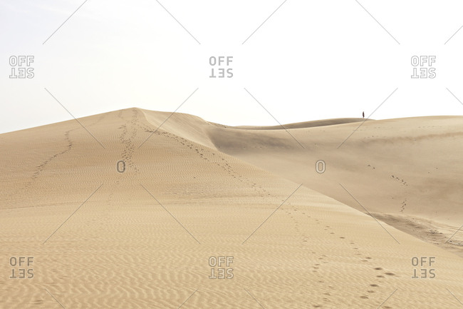 Large dunes in desert with person in horizon