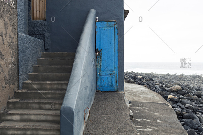 San Andres, Gran Canaria, Canary Islands, Spain - December 2, 2017: Narrow blue door by the sea side