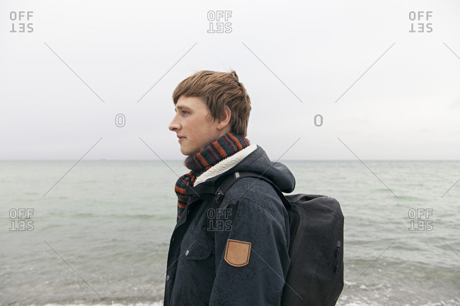 Young man walking in rain by the sea
