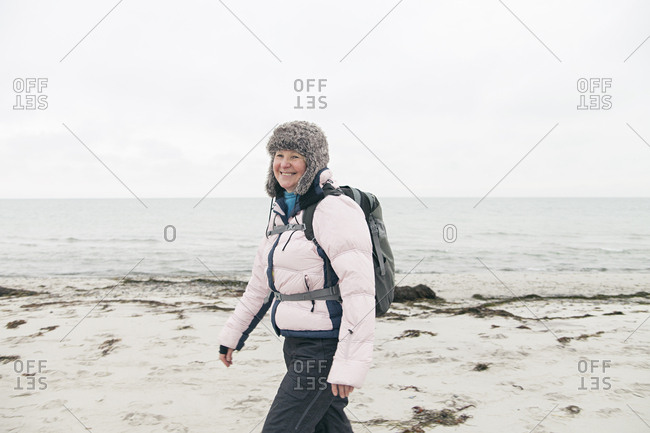 Woman in winter clothes and fur hat walking by the beach