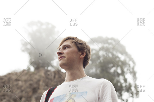 Young man looking to the left in misty environment