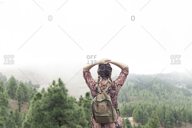 Girl looking out at misty forest landscape