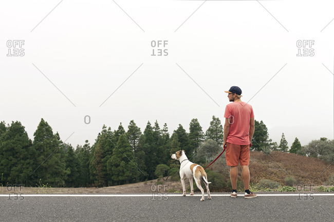 Man with dog standing on the road by the forest looking to the side