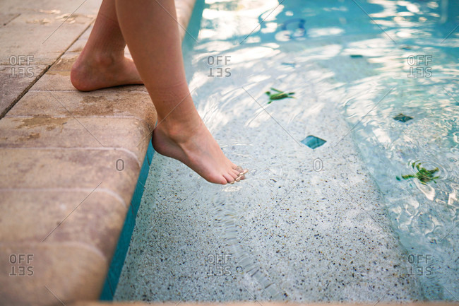 Girl dipping her toes into the water of a swimming pool