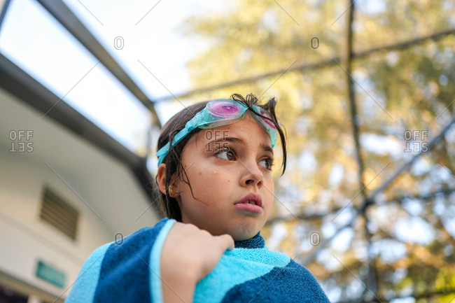 Portrait of a girl wrapped in a towel with swimming goggles on her head