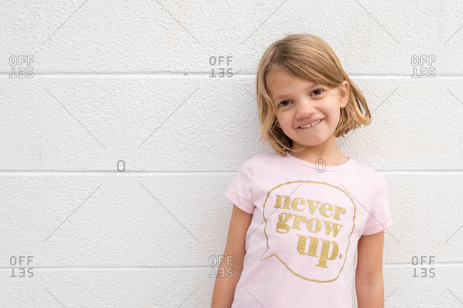 Portrait of a smiling girl wearing a t-shirt standing against a white wall