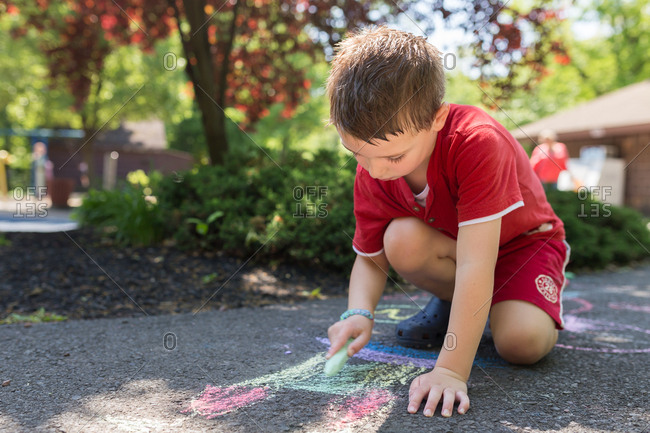 Boy drawing with chalk at a playground