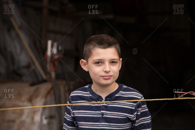 Boy standing behind a rope at a farm