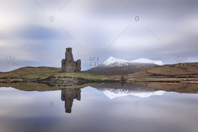 Ardvreck Castle and mountains reflecting off Loch Assynt, Scotland