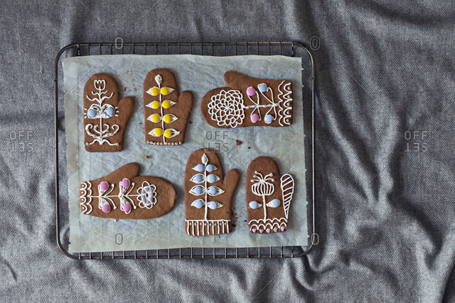 Decorated gingerbread mittens on baking sheet