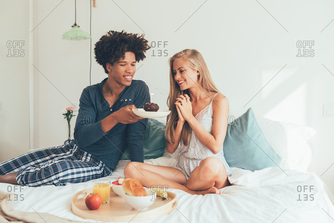 Young beautiful interracial couple having a surprise birthday breakfast in bed