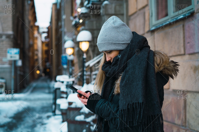 Side view of pretty woman in casual warm clothes using smartphone on city street.