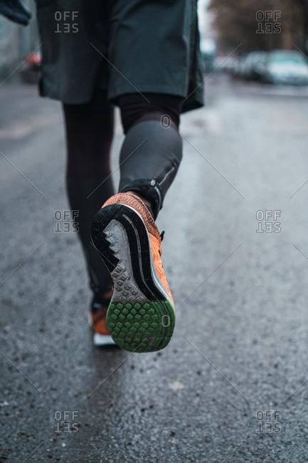 Crop unrecognizable man in warm sportswear walking on street.