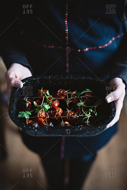 Crop person holding small baking pan full of palatable dried tomatoes.