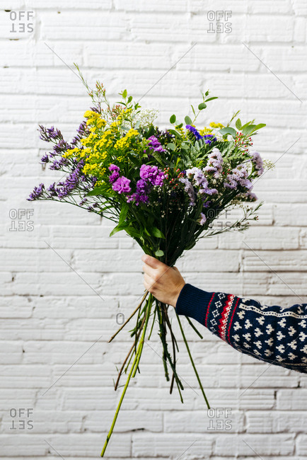 Crop hand holding elegant flower bouquet on background of white brick wall.