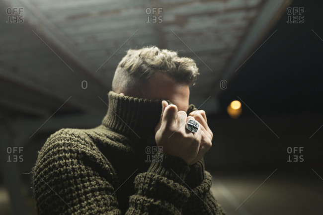 Unrecognizable man taking off or closing face with green warm sweater on parking lot at night.