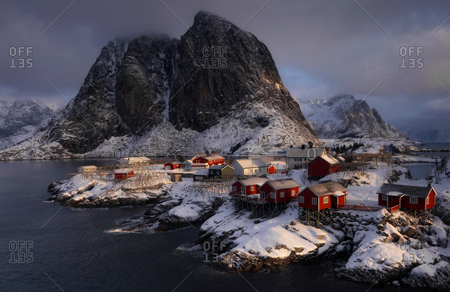 View to small red houses in village on lake shore in mountains covered with snow.