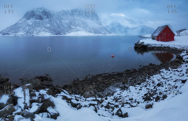 View to wooden red house on shore of lake in mountains covered with snow.