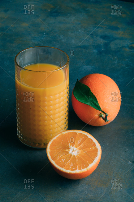 Fresh oranges and glass with orange juice