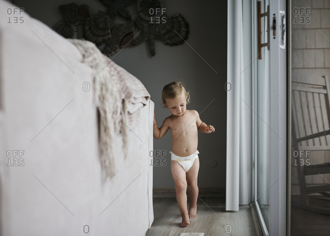 Toddler wearing diaper walking behind couch