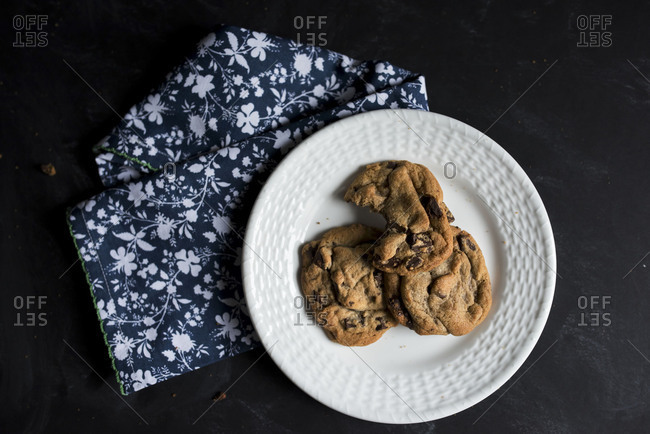 Freshly baked chocolate chip cookies on a plate with a bite missing from one