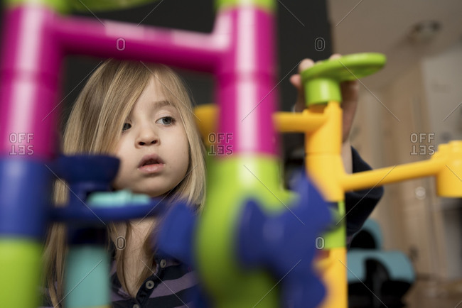 Young girl looking at toy tower