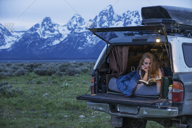 Young woman reading book while relaxing in motor home at forest