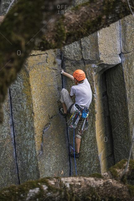 Rear view of hiker rock climbing