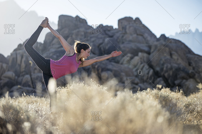 Woman standing on one leg while practicing yoga on field against mountains