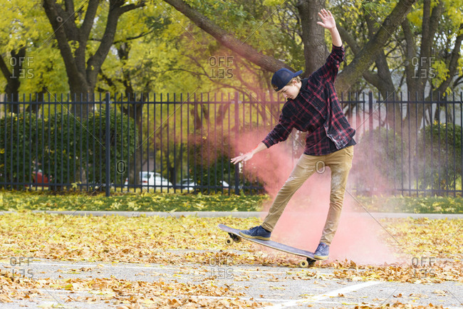 Teenage boy with powder paint skateboarding on footpath at park during autumn