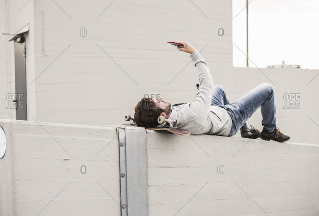Full length of man taking selfie while lying on retaining wall