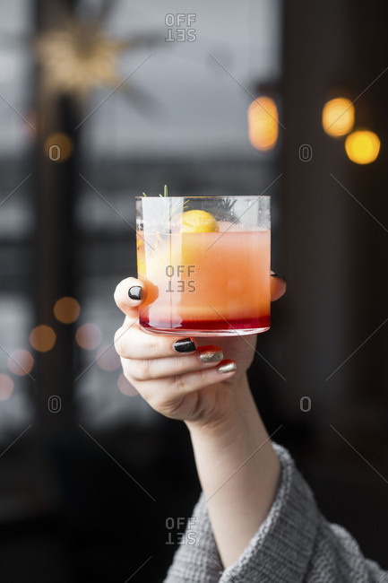 Woman holding up beverage for toast