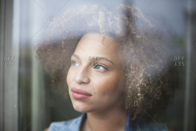 Close-up of thoughtful woman with curly hair seen through glass window