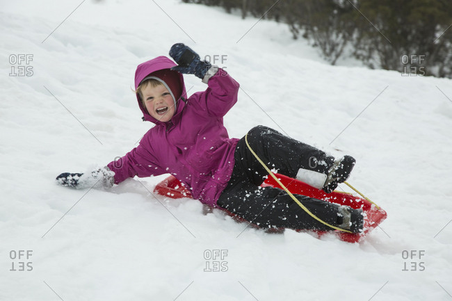 Cheerful boy tobogganing on snow covered field