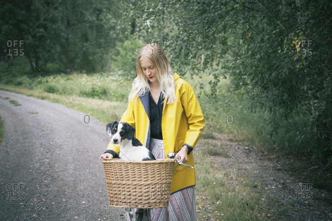 Woman holding bicycle with dog in basket on dirt road at forest