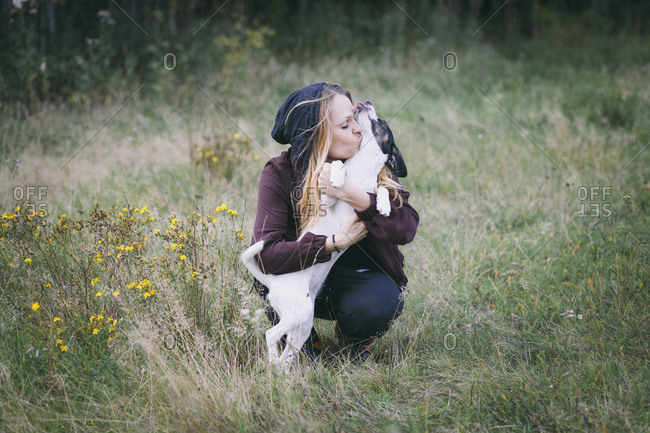 Woman kissing dog while crouching in grassy field