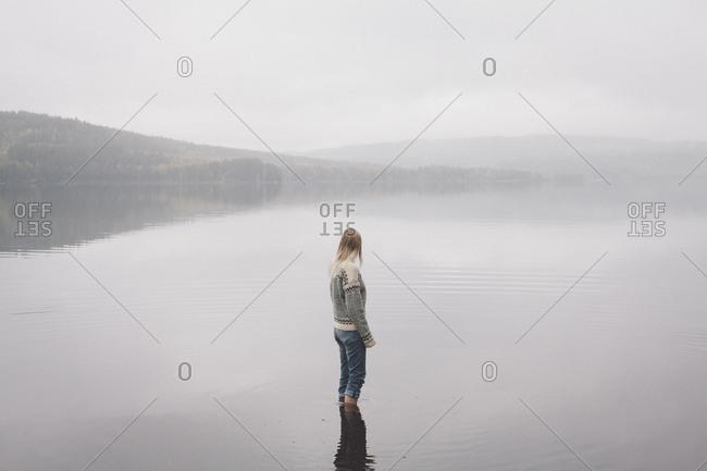 Woman standing in lake against sky during foggy weather, Jaervsoe, Haelsingland, Sweden