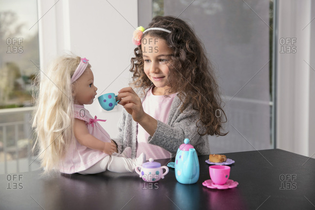 Portrait of smiling little girl playing with doll and doll's china set