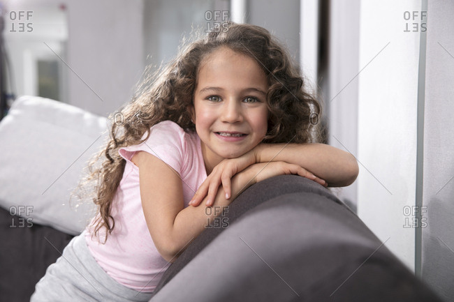 Portrait of smiling little girl with tooth gap on the couch