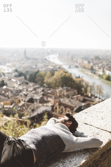 Italy- Verona- tourist lying on balustrade