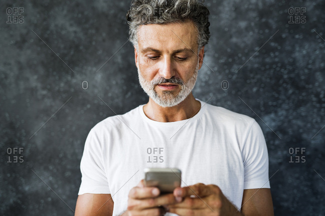 Mature man using smartphone- sending text messages