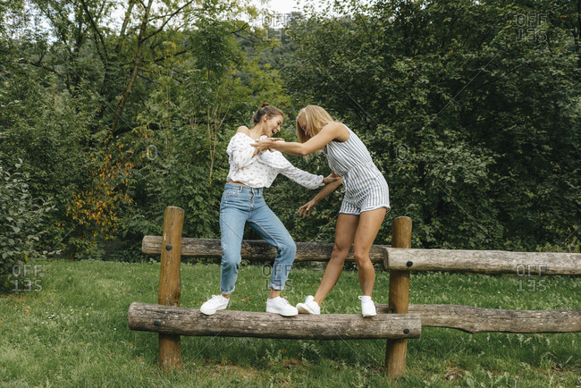 Two happy young women balancing on fence in a park