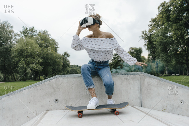 Young woman with skateboard wearing VR glasses in a skate park