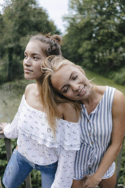 Smiling young woman resting on female friend's shoulder