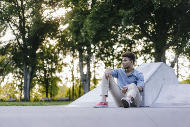 Portrait of relaxed man sitting in skate park